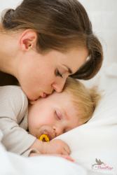 אמא מנשקת תינוק עם מוצץ